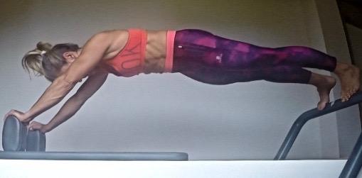 Emma coach Pilates sur reformer plank